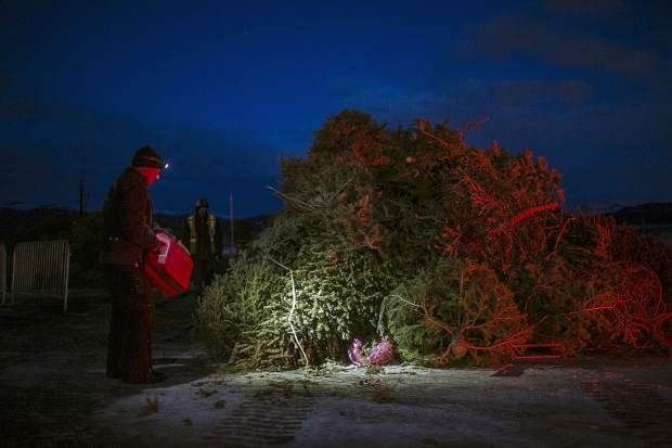 A man douses the Christmas trees with fuel for the Spontaneous Combustion event Saturday, Jan. 20, at the Frisco Marina.