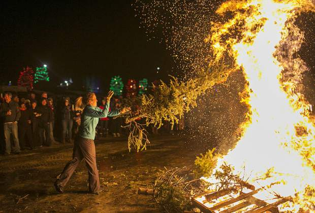 Nora Gilbertson tosses a Christmas tree into the bonfire during the Spontaneous Combustion event Saturday, Jan. 20, at the Frisco Marina. The Christmas trees were donated by the community for the annual event.