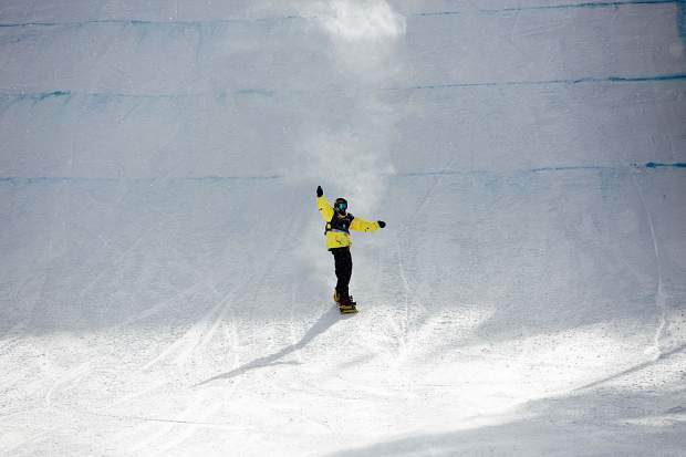 Kyle Mack raises his arm in celebration after landing the final jump on his final run at Saturday's Toyota U.S. Grand Prix at Mammoth Mountain, California. Mack's run was good enough for first place at the final 2018 Olympic qualifying event, effectively clinching his berth on the U.S. snowboard slopestyle and big air team for next month's Pyeongchang Winter Olympics in South Korea.