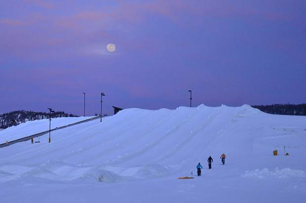 Scott Pohlman, Eric Bensen and Ruth Meade climb a hill at Frisco Adventure Park while testing out some fat bikes under Tuesday night's full moon. The trio all said they impressed with how well the bikes handled on the pack snow.