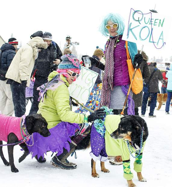 Shannon Jacoby, in purple skirt, and Michelle, in grey skirt, interact with their dogs Kola, in pink, and Quito, in green, during the Mardi Gras 4Paws Parade Saturday, Feb. 10, along Main Street in Frisco.