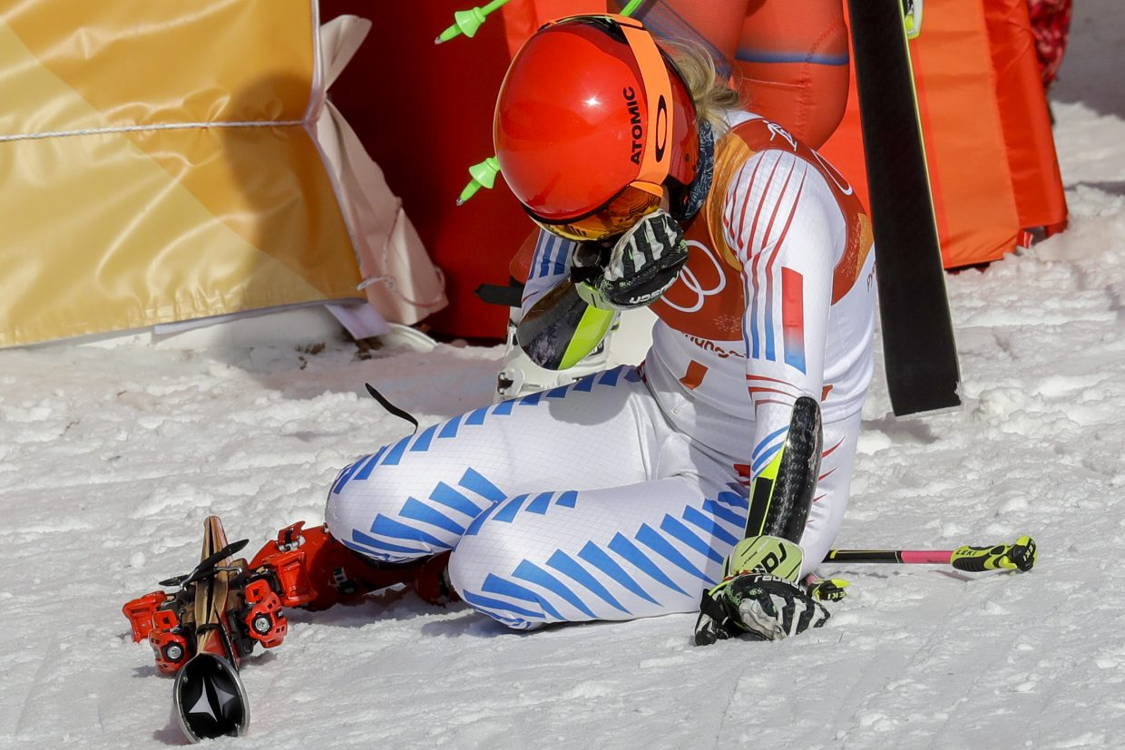 Mikaela Shiffrin, of the United States, falls to her knees after winning the gold medal in the Women's Giant Slalom at the 2018 Winter Olympics in Pyeongchang, South Korea, Thursday, Feb. 15, 2018., Thursday, Feb. 15, 2018. (AP Photo/Michael Probst)