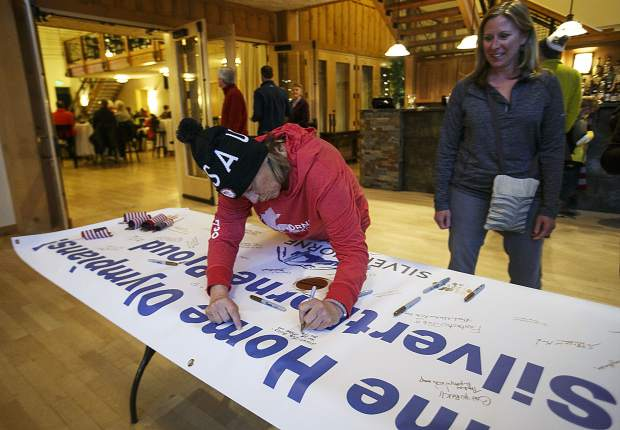 Silverthorne resident Ann-Marie Sandquist writes supporting comments on a poster for the local Olympians competing in the Snowboard Big Air competition at the Winter Olympics in South Korea during a watching party at the Silverthorne Pavilion Tuesday, Feb. 20.