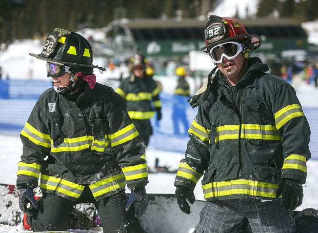 Brighton Fire Department firefighters on snowboards share a laugh while participating in the 12th annual Fire Hose Relay Race Friday, Feb. 23, at Arapahoe Basin Ski Area.