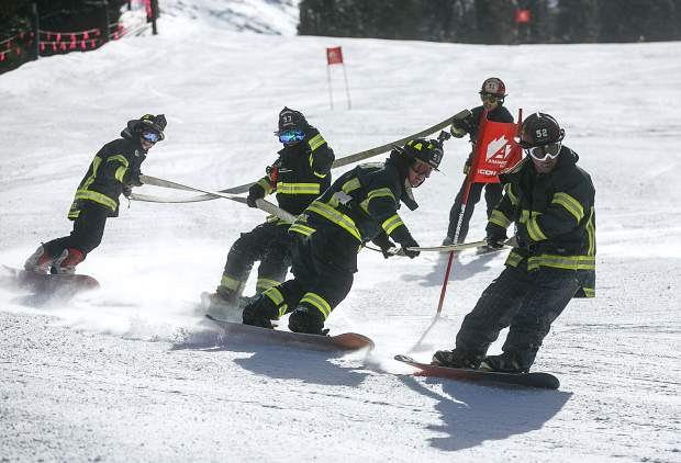 Brighton Fire Department's firefighters race around slalom gates on snowboards while holding a firehose in the 12th annual Fire Hose Relay Race Friday, Feb. 23, at Arapahoe Basin Ski Area.