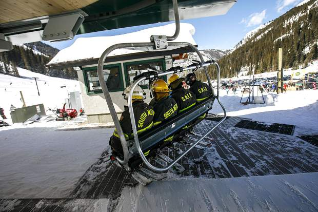 People in firefighting suits take off on a chairlift for the 12th annual Fire Hose Relay Race Friday, Feb. 23, at Arapahoe Basin Ski Area.