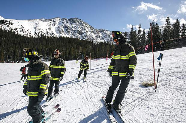 Red, White, and Blue Fire Department's interact before taking off for the slalom gates in the 12th annual Fire Hose Relay Race Friday, Feb. 23, at Arapahoe Basin Ski Area.