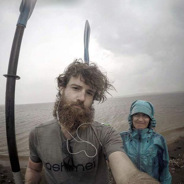 Callie Morgigno of Leadville and Charlie Walker of England pose for a photo with their kayak paddles despite the rain on the Ural River in Russia.