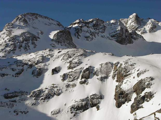 Late spring snow clings to the bubble basin rock cliffs in the Gore Range.