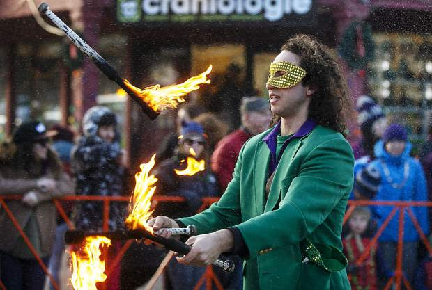 A juggler walks along with the Mardi Gras parade floats on Main Street in Breckenridge Tuesday, Feb. 13.