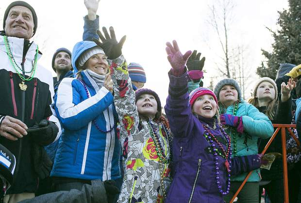 Visitors read out to catch the flying beads during the Mardi Gras parade on Main Street in Breckenridge Tuesday, Feb. 13.
