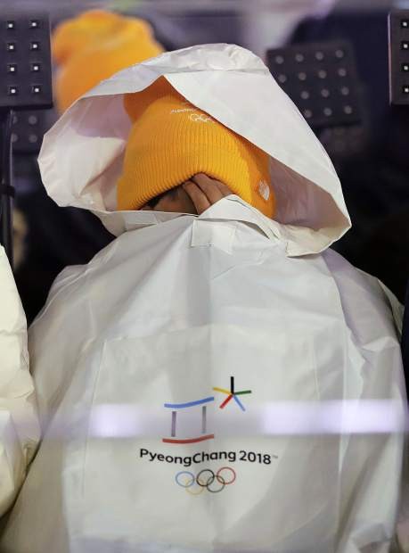 A young spectator tries to keep warm during the opening ceremony of the 2018 Winter Olympics in Pyeongchang, South Korea on Friday, Feb. 9