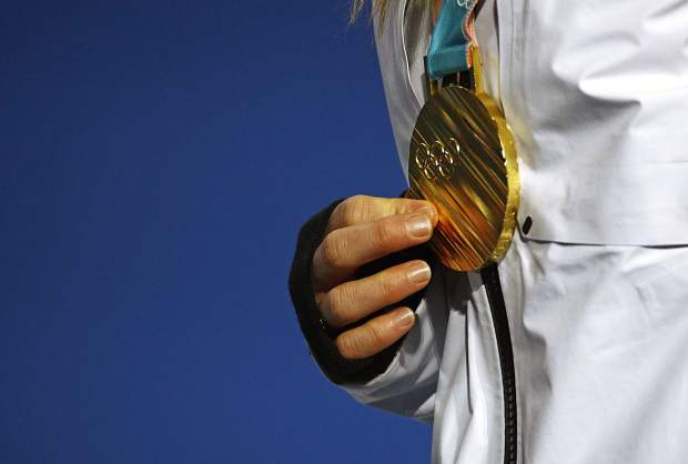 Women's slopestyle gold medalist Jamie Anderson, of the United States, holds her medal during a medal ceremony at the 2018 Winter Olympics in Pyeongchang, South Korea, Monday, Feb. 12, 2018.
