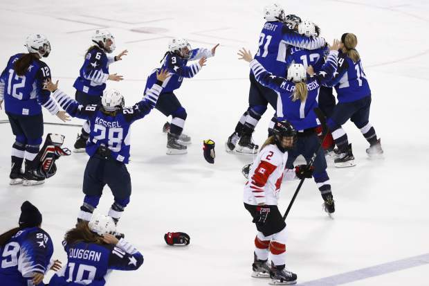 Canada's Meghan Agosta(2) skates away as the United States players celebrate after winning the women's gold medal hockey game against Canada at the 2018 Winter Olympics in Gangneung, South Korea, Thursday, Feb. 22, 2018. (AP Photo/Jae C. Hong)