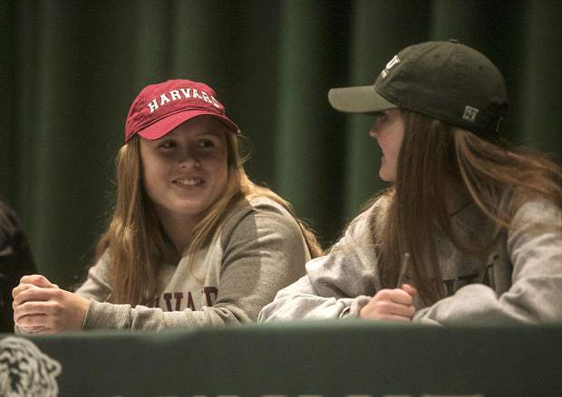 Summit High student-athletes Cassidy Bargell and Shannon Hogeman smile at each other during Wednesday's National Signing Day ceremony at the high school's auditorium. Bargell will play rugby at Harvard while Hogeman will play soccer at Illinois Wesleyan.