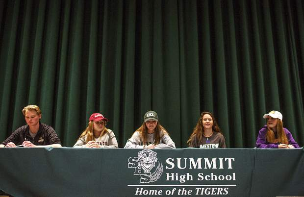 Summit High student-athletes (from left to right) Sean Gurlea, Cassidy Bargell, Shannon Hogeman, Tanner McCann and Haleigh Lecklitner take part in the school's National Signing Day ceremony, officially announcing which colleges they will attend next year, on Wednesday in the high school's auditorium.