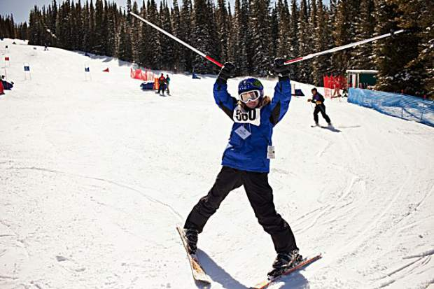 A Special Olympics athlete hoists up ski poles during the annual event at Copper Mountain Ski Resort.