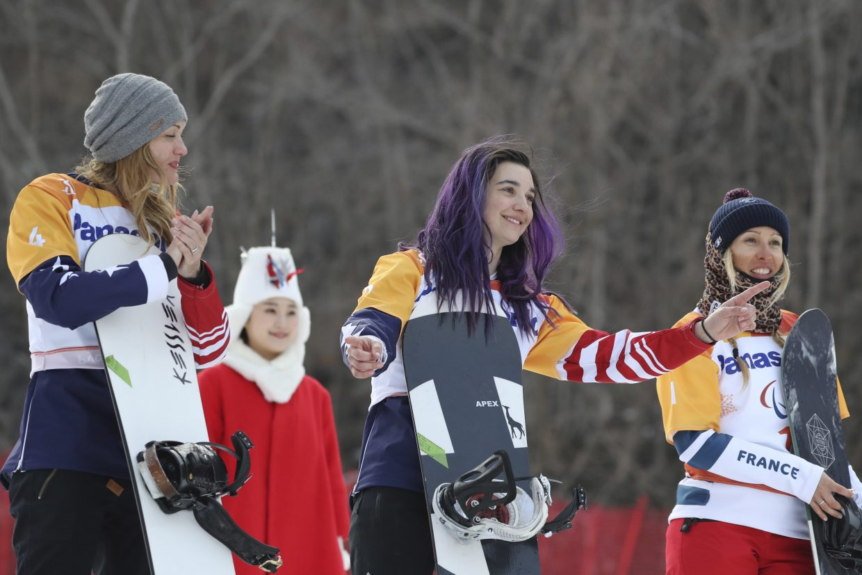 Winners of the Women's Snowboard Cross SB-LL1 event from left silver medalist Amy Purdy of United States, gold medalist Brenna Huckaby of United States and bronze medalist Cecile Hernandez of France pose for photos during a ceremony at the 2018 Winter Paralympics at the Jeongseon Alpine Centre in South Korea, Monday, March 12, 2018.