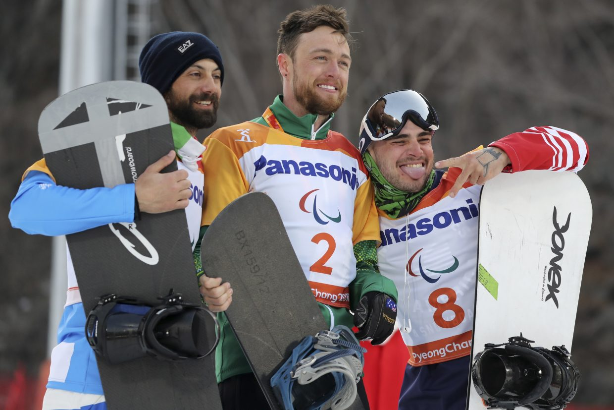 Men's Snowboard Cross SB-UL event winners from left, silver medalist Manuel Pozzerle of Italy, gold medalist Simon Patmore of Australia and bronze medalist Mike Minor of United States pose for photos during a ceremony at the 2018 Winter Paralympics in Pyeongchang, South Korea, Monday, March 12, 2018.