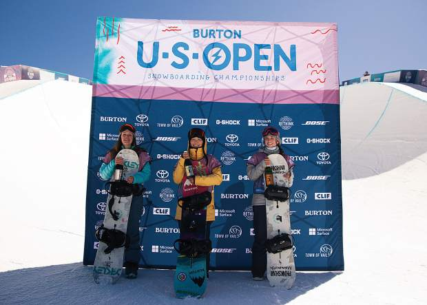 Japanese youngster Mitsuki Ono (center) stands atop the podium after winning the Burton U.S. Open Junior Jam halfpipe snowboarding competition, alongside Americans Tessa Maud (left, second-place, 77.24) and Kinsley White (third-place, 75.00).