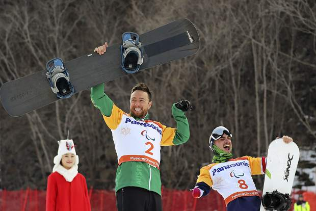 Men's Snowboard Cross SB-UL event gold medalist Simon Patmore of Australia, center celebrates as bronze medalist Mike Minor of Frisco cheer for him during a ceremony at the 2018 Winter Paralympics in Pyeongchang, South Korea, Monday, March 12, 2018.