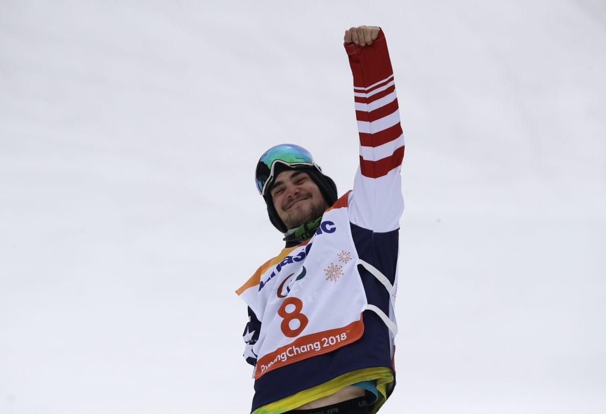 Gold medal winner Mike Minor of the United States celebrates during the victory ceremony for the the men's snowboard banked slalom sb-ul at the 2018 Winter Paralympics in Jeongseon, South Korea, Friday, March 16, 2018.