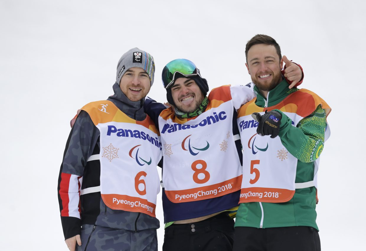 Gold medal winner Mike Minor of the United States, center, silver medal winner Patrick Mayrhofer of Austria, left, and bronze medal winner Simon Patmore of Australia pose for the media during the victory ceremony for the the men's snowboard banked slalom sb-ul at the 2018 Winter Paralympics in Jeongseon, South Korea, Friday, March 16, 2018.