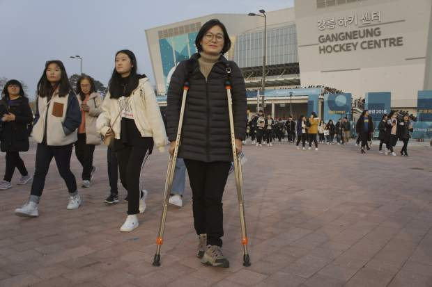 In this March 12, 2018, photo, South Korean Park Mi-ae poses in front of the Gangneung Hockey Center in Gangneung, South Korea. Park, a 53-year-old Gangneung resident who came to a hockey game on crutches while recovering from a foot injury, hoped that the experience of accommodating a large number of disabled people and athletes will help make her city a safer and friendlier place for the disabled. The thousands from across the country who volunteered for the games could help initiate changes at their homes too, she said.