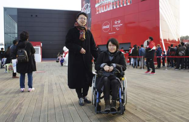 In this March 12, 2018, photo, Japan's Tomoko Inujima, right, poses with her husband Yoshihiro Nakabo near the Gangneung Hockey Center in Gangneung, South Korea. Inujima, a wheelchair user from Tokyo who came to the games with her husband, said she ran into trouble entering restaurants and stores. However, she said the help from volunteer workers and local residents, who she found attentive and supportive, more than made up for it.