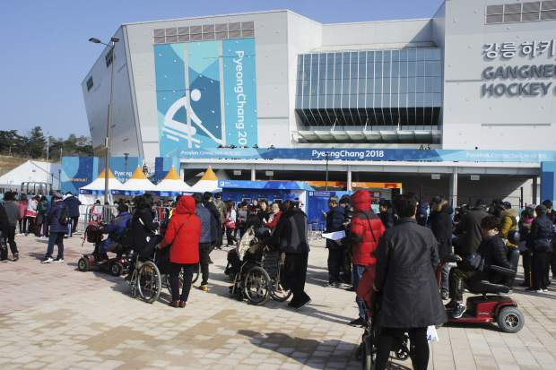 In this March 11, 2018, photo, people in wheelchairs wait to enter the Gangneung Hockey Center in Gangneung, South Korea. When the Paralympics ended Sunday, March 18 with the closing ceremony at the soon-to-be-demolished Olympic Stadium, South Korea faced questions about the event's legacy.