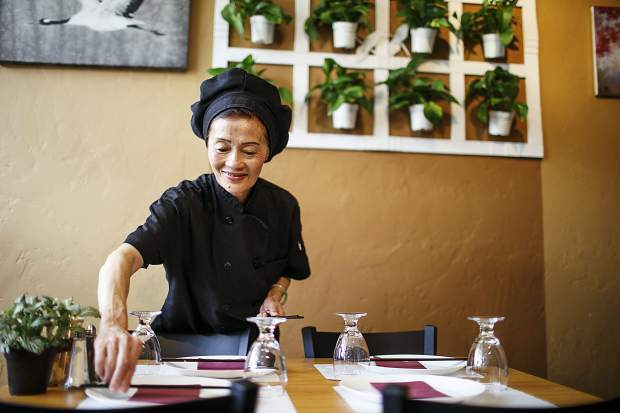 Lien Nguyen, who is the chef and mother of three at Peak of Asia, set the tables at new vietnamese restaurant Thursday, March 8, in Breckenridge.