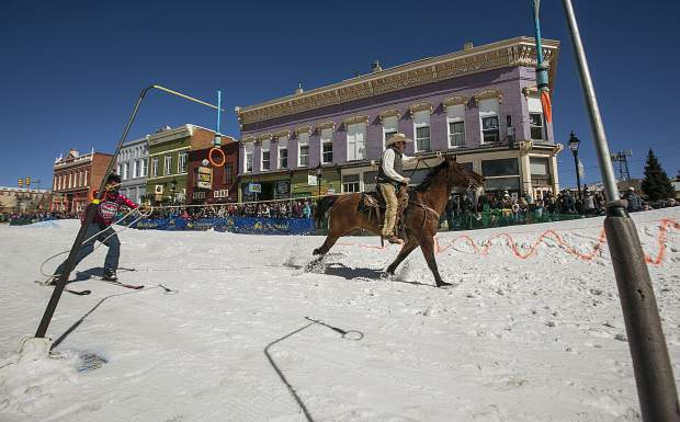 A horse and rider pull a skier as he collects rings with a baton during the 70th annual skijoring competition Saturday, March 3, on Main Street in Leadville.