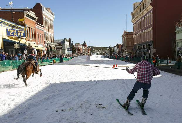 A horse and rider pull a skier into the obstacle course in the 70th annual skijoring competition Saturday, March 3, on Main Street in Leadville.