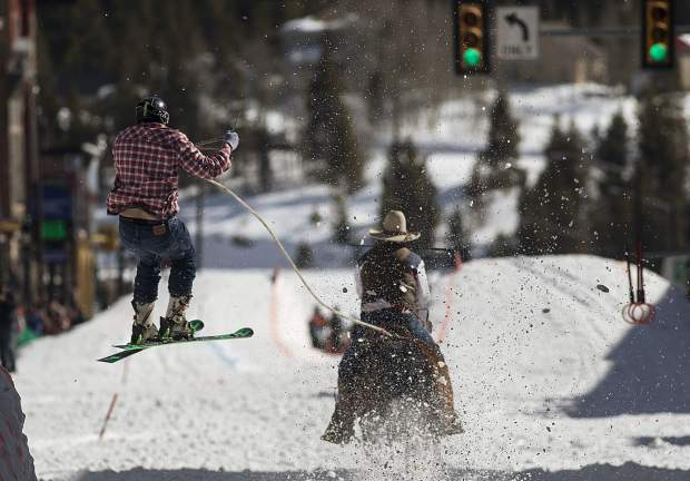 A horse and rider pull a skier off a jump during the 70th annual skijoring competition Saturday, March 3, on Main Street in Leadville.