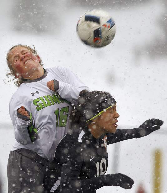 Summit High School sophomore midfielder Samantha Cheek attempts to head the ball over Grand Junction High School senior midfielder Tanner McCann during the home match Thursday, March 29, in Frisco.