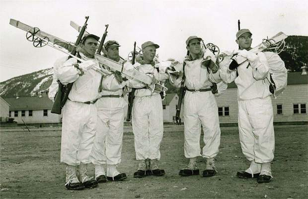 Members of the10th Mountain Division hold their skis, poles and rifles over their shoulders while posing for a picture at Camp Hale in Pando, Colorado during World War II.