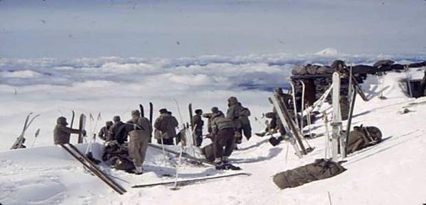 With their rifles over their right shoulders, members of the 10th Mountain Division march out into the snow during World War II.