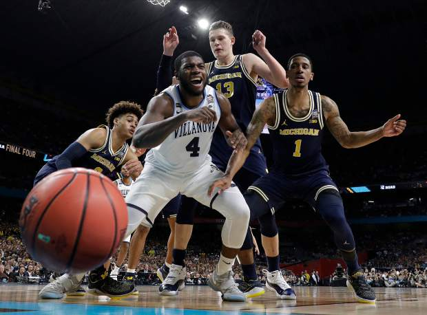 Villanova's Eric Paschall (4) reacts as he loses the control of the ball against Michigan's Moritz Wagner (13) and Charles Matthews (1) during the first half in the championship game of the Final Four NCAA college basketball tournament, Monday, April 2, 2018, in San Antonio.