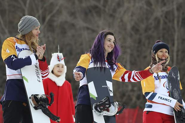Winners of the Women's Snowboard Cross SB-LL1 event from left include: silver medalist Amy Purdy of the United States, gold medalist Brenna Huckaby of the United States and bronze medalist Cecile Hernandez of France. The trio pose for photos during a ceremony at the 2018 Winter Paralympics at the Jeongseon Alpine Centre in South Korea, Monday, March 12, 2018.