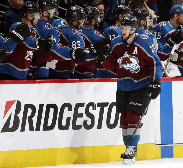 Colorado Avalanche center Nathan MacKinnon, front, is congratulated after scoring a goal against the Nashville Predators as he passes the team box in the second period of Game 3 of an NHL hockey first-round playoff series on Monday, April 16, 2018, in Denver.