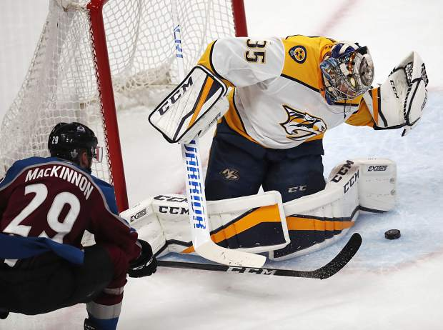 Colorado Avalanche center Nathan MacKinnon, front, has his shot stopped by Nashville Predators goaltender Pekka Rinne during the third period of Game 4 of an NHL hockey first-round playoff series Wednesday, April 18, 2018, in Denver. The Predators won 3-2.