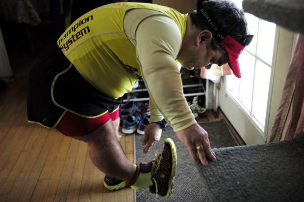 In this Thursday, March 15, 2018, photo, marathon runner John Young, of Salem, Mass., puts on his running shoes before a training run, in Salem. Young was born with dwarfism, but that hasn't stopped him from conquering multiple marathons and triathlons. While most marathoners take about 35,000 steps to reach the finish line, Young uses about 80,000.