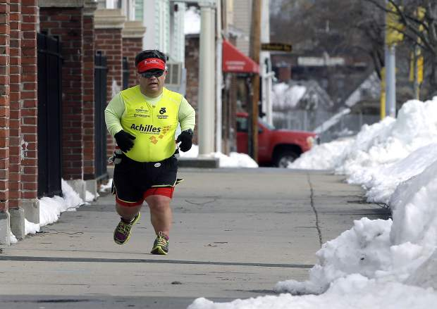 In this Thursday, March 15, 2018, photo, marathon runner John Young, of Salem, Mass., makes his way along a training route in Salem. Young was born with dwarfism, but that hasn't stopped him from conquering multiple marathons and triathlons. While most marathoners take about 35,000 steps to reach the finish line, Young uses about 80,000.