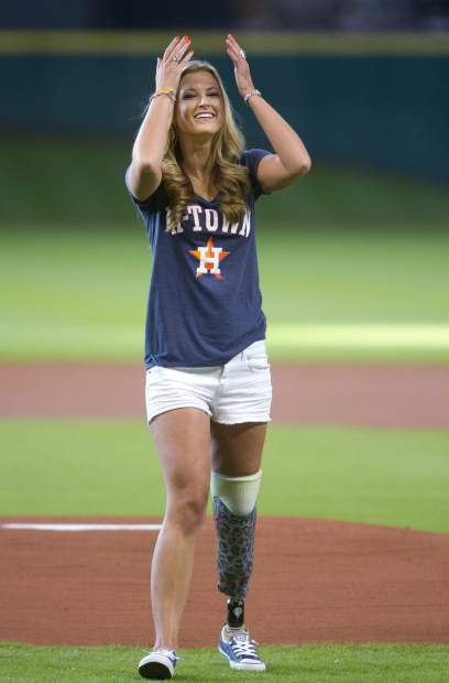 FILE - In this July 21, 2015 file photo, Rebekah Gregory, who lost her leg in the Boston Marathon bombing, reacts after her throw fell short on a ceremonial first pitch before a baseball game between the Boston Red Sox and Houston Astros in Houston. After her first marriage ended in divorce, she married her college sweetheart and moved to Houston. She established the Rebekah's Angels Foundation to help children with post-traumatic stress disorder, and wrote a book,
