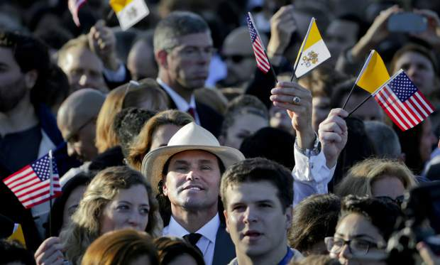 FILE - In this Sept. 23, 2015 file photo, Carlos Arredondo, center, waves Vatican and U.S. flags as he waits on the South Lawn of the White House in Washington for the arrival of Pope Francis. Arredondo helped save the life of marathon spectator Jeff Bauman after the 2013 Boston Marathon bombings. Arredondo volunteers with the Red Cross, and his family foundation works to prevent military-related suicides. He is preparing to run in his first Boston Marathon on April 16, 2018. (AP Photo/Pablo Martinez Monsivais, File)