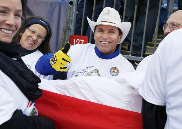 FILE - In this Nov. 26, 2017 file photo, Carlos Arredondo, center, gives a thumbs-up before participating in a Salute to Service military appreciation campaign before an NFL football game between the New England Patriots and the Miami Dolphins in Foxborough, Mass. Arredondo helped save the life of marathon spectator Jeff Bauman after the 2013 Boston Marathon bombings. He now volunteers with the Red Cross, and his family foundation works to prevent military-related suicides. He is preparing to run in his first Boston Marathon on April 16, 2018. (AP Photo/Michael Dwyer, File)