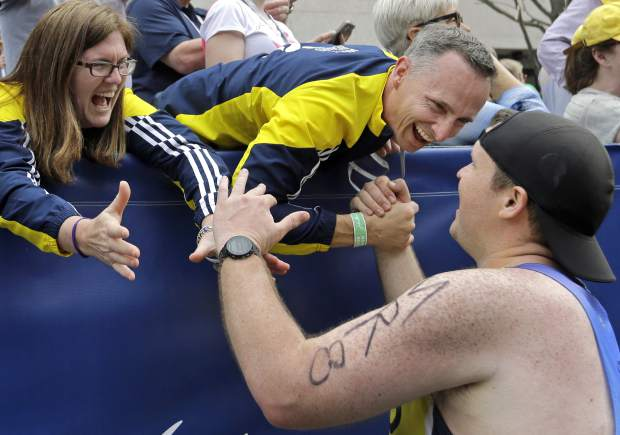 FILE - In this April 17, 2017 file photo, Denise, left, and Bill Richard greet a runner who ran in the Boston Marathon for Team MR8, a foundation to honor of their son Martin, killed in the 2013 Boston Marathon bombings. Besides setting up the foundation, they helped create a new park in Martin's memory in downtown Boston where children can play. (AP Photo/Elise Amendola, File)