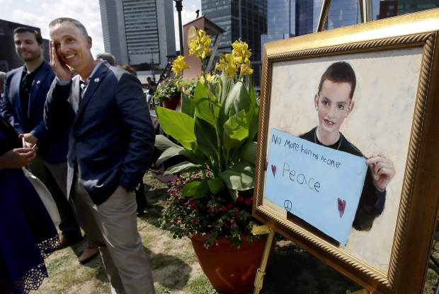 FILE - In this Aug. 16, 2017 file photo, Bill Richard, second from left, stands beside a painting of his son Martin Richard, the youngest person killed in the Boston Marathon bombing, at the conclusion of groundbreaking ceremonies for a Boston park named in Martin's honor. Besides the park, the family has also set up a foundation in Martin's memory. (AP Photo/Steven Senne, File)