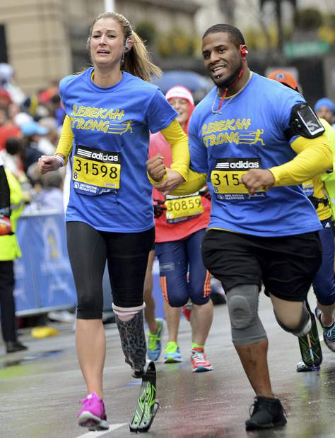In this April 20, 2015 photo, Boston Marathon bombing survivor Rebekah Gregory, left, finishes the Boston Marathon on her prosthetic left leg with her trainer Artis Thompson in Boston. After her first marriage ended in divorce, Rebekah married her college sweetheart and moved to Houston. She established the Rebekah's Angels Foundation to help children with post-traumatic stress disorder, and wrote a book,