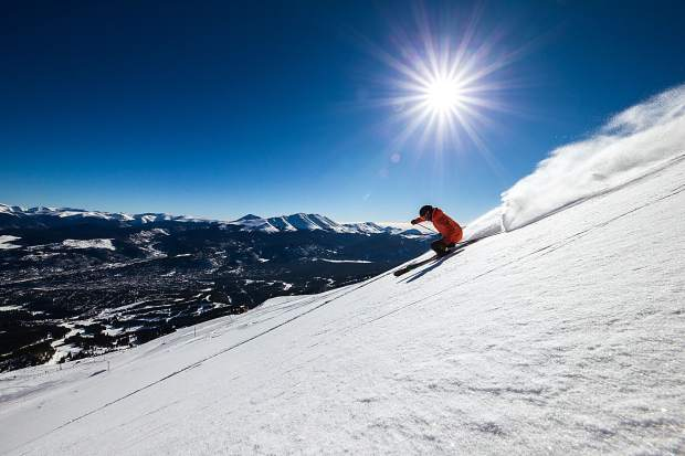 A skier descends a slope at Breckenridge Ski Resort under bluebird skies in early March.